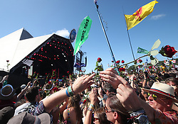 The crowd are handed out roses during a duet between Kylie Minogue with guest Nick Cave on the Pyramid Stage on the fifth day of the Glastonbury Festival at Worthy Farm in Somerset.