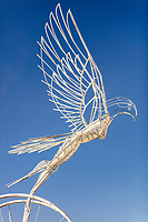 "Taking Flight<br /> by: Nicki Adani<br /> from: Mill Valley, CA<br /> year: 2019<br /> <br /> Nicki Adani's ""Taking Flight"" emboldens visitors to be who they truly are, inspiring them to leave behind what is holding them back. A 10-foot tall feminine bird-like figure, welded from raw steel rods and tubes, her wings spread wide, takes flight from her perch upon a 10-foot tall spoked wheel, representing the circle of life. Viewers interact by making colorful ropes and weaving them into the wheel as a metaphor of releasing one's past. Experiences already lived through can't be erased, but they can speak their truths, and be let go. In the process, individuals can connect to their inner strength allowing them to spread their wings to fly free.<br /> <br /> URL: http://time2flyart.com<br /> Contact: nicki@time2flyart.com<br /> <br /> https://burningman.org/event/brc/2019-art-installations/?yyyy=&artType=H#a2I0V000001AW74UAG"