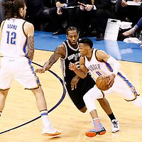 08 May 2016: Oklahoma City Thunder guard Russell Westbrook (0) drives past San Antonio Spurs forward Kawhi Leonard (2) on a screen set by Oklahoma City Thunder center Steven Adams (12) during the Oklahoma City Thunder 111-97 victory over the San Antonio Spurs, during Game Four of the Western Conference Semifinals of the NBA Playoffs at the Chesapeake Energy Arena, Oklahoma City, Oklahoma, USA.