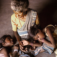 Vijyashree (left, age 7) and Vijitha Viswanathan (age 9) with their maternal grandmother Govindammal (age 70) at her home in the Pudhupattinam tsunami temporary relief camp.<br /><br />These photographs encompass four years in the lives of two families of children from South India who lost their mothers to the Asian tsunami. Following that momentous event in 2004, the five Krishnamurthy sisters from Puddupettai went to live in the Cuddalore Government Special Home for Tsunami Children. And Vijitha and Vijyashree Viswanathan, after an initial brief spell at the same home, now live with their father and his new wife in the nearby fishing village of Thalanguda. <br /><br />Each child affected by the tsunami had to adapt to changed circumstances and cope with emotions no one in their family could have possibly anticipated. The younger children seemed to adjust more quickly than their older siblings. And, while grief rendered some silent, in others it provoked a real sense of anger. Some became withdrawn while others craved attention and resorted to disruptive behavior. For all of the children, the experience of losing a parent seemed to strengthen the bond they shared with their brothers and sisters. <br /><br />The loss of a parent meant that some of the children photographed in this project inherited responsibilities that, while often a burden, provided a distraction from their own painful emotions. Sivaranjini Krishnamurthy lost her mother to the tsunami and then, together with her four younger sisters was abandoned by her father. At eleven years of age she took on the role of a mother to her younger sisters. Though she attends school and receives the support of orphanage staff, Sivaranjini has sacrificed much of her own childhood to take care of them. <br /><br />For Sivaranjini and the other children whose experiences are presented here, the tsunami is a defining event in their lives; the terrible personal upheaval they have suffered will inevitably shape all of th