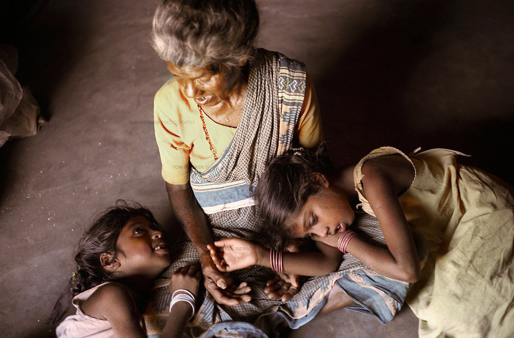 Vijyashree (left, age 7) and Vijitha Viswanathan (age 9) with their maternal grandmother Govindammal (age 70) at her home in the Pudhupattinam tsunami temporary relief camp.<br />