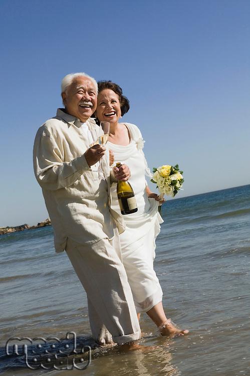 Senior Newlyweds Walking in Ocean