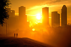Stock photo of sunrise with two joggers along Buffalo Bayou Hike and Bike trail in front of the Houston,Texas skyline
