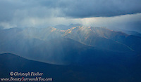 Intense rain showers sweep across the foothills of the Yukon's Peel Watershed, but they are not enough to stop the soft golden glow of these beautiful mountain peaks from showing through.