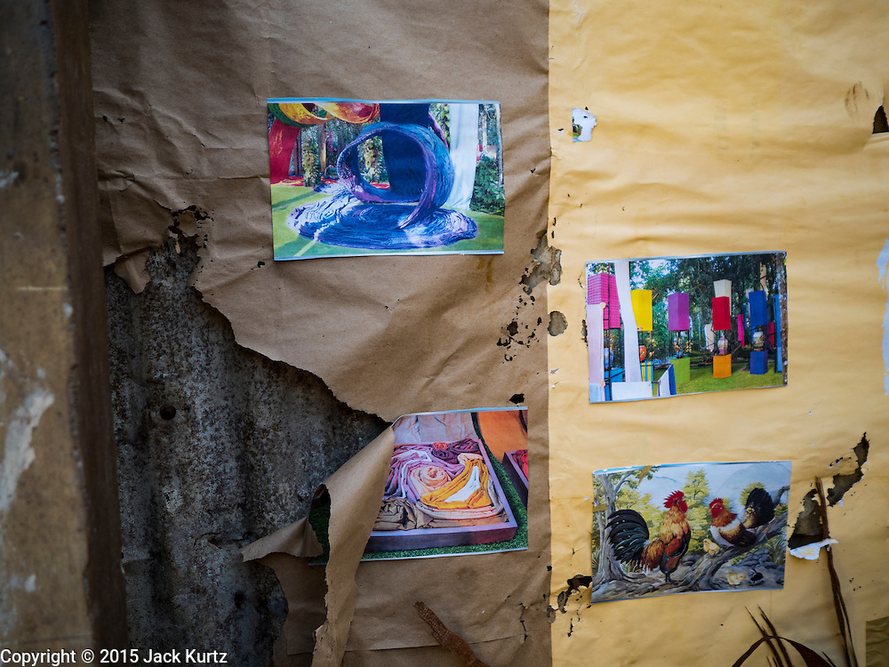 14 OCTOBER 2015 - BANGKOK, THAILAND: Pictures on the last wall standing in a destroyed home in the Wat Kalayanamit neighborhood. Fifty-four homes around Wat Kalayanamit, a historic Buddhist temple on the Chao Phraya River in the Thonburi section of Bangkok, are being razed and the residents evicted to make way for new development at the temple. The abbot of the temple said he was evicting the residents, who have lived on the temple grounds for generations, because their homes are unsafe and because he wants to improve the temple grounds. The evictions are a part of a Bangkok trend, especially along the Chao Phraya River and BTS light rail lines. Low income people are being evicted from their long time homes to make way for urban renewal.         PHOTO BY JACK KURTZ