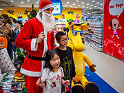01 DECEMBER 2018 - BANGKOK, THAILAND: A Thai man in Santa Claus outfit poses for pictures with children at the Toys R Us store in Central World in Bangkok. Toys R Us closed all of their brick and mortar stores in the United States in 2018 but kept many of their overseas stores open.     PHOTO BY JACK KURTZ