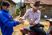 12 MARCH 2013 - ALONG HIGHWAY 13, LAOS: An ice cream vendor sells a couple of ice cream cones to a woman on Highway 13 in rural Laos. The paving of Highway 13 from Vientiane to near the Chinese border has changed the way of life in rural Laos. Villagers near Luang Prabang used to have to take unreliable boats that took three hours round trip to get from the homes to the tourist center of Luang Prabang, now they take a 40 minute round trip bus ride. North of Luang Prabang, paving the highway has been an opportunity for China to use Laos as a transshipping point. Chinese merchandise now goes through Laos to Thailand where it's put on Thai trains and taken to the deep water port east of Bangkok. The Chinese have also expanded their economic empire into Laos. Chinese hotels and businesses are common in northern Laos and in some cities, like Oudomxay, are now up to 40% percent. As the roads are paved, more people move away from their traditional homes in the mountains of Laos and crowd the side of the road living off tourists' and truck drivers.    PHOTO BY JACK KURTZ