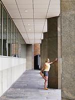 Woman stretching against a pillar