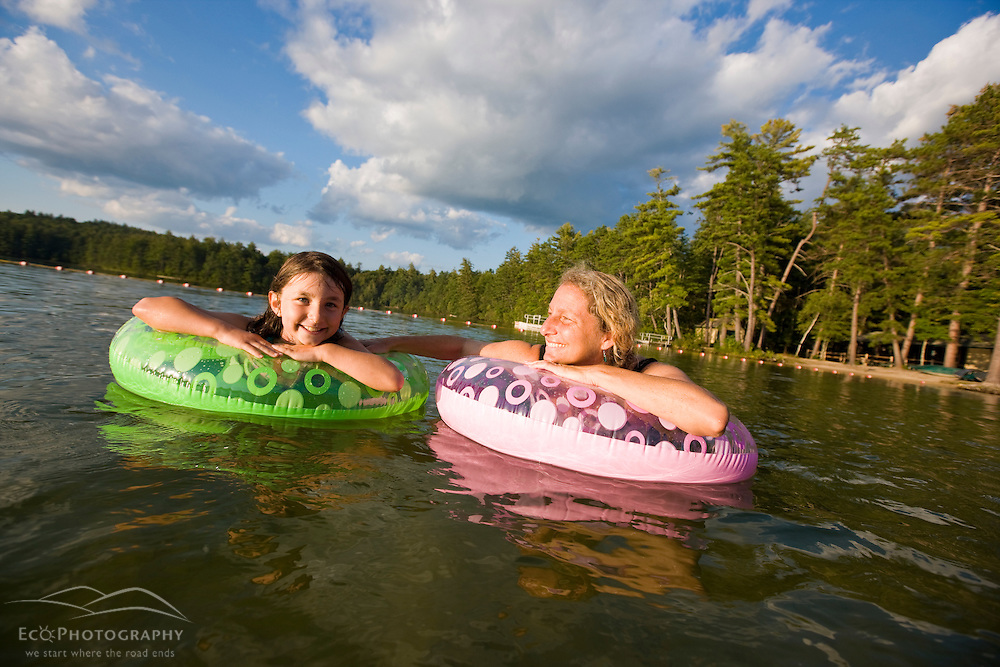A woman and her daughter float at the beach at White Lake State Park in Tamworth, New Hampshire.