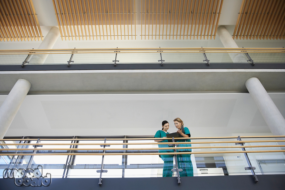 Medical workers looking at chart on balcony low angle view