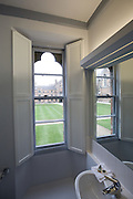 View from washroom to quod with shutters open and window reflected in mirror