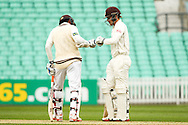 Kumar Sangakkara and Rory Burns of Surrey County Cricket Club bump gloves during the LV County Championship Div Two match at the Kia Oval, London<br /> Picture by Mark Chappell/Focus Images Ltd +44 77927 63340<br /> 26/04/2015