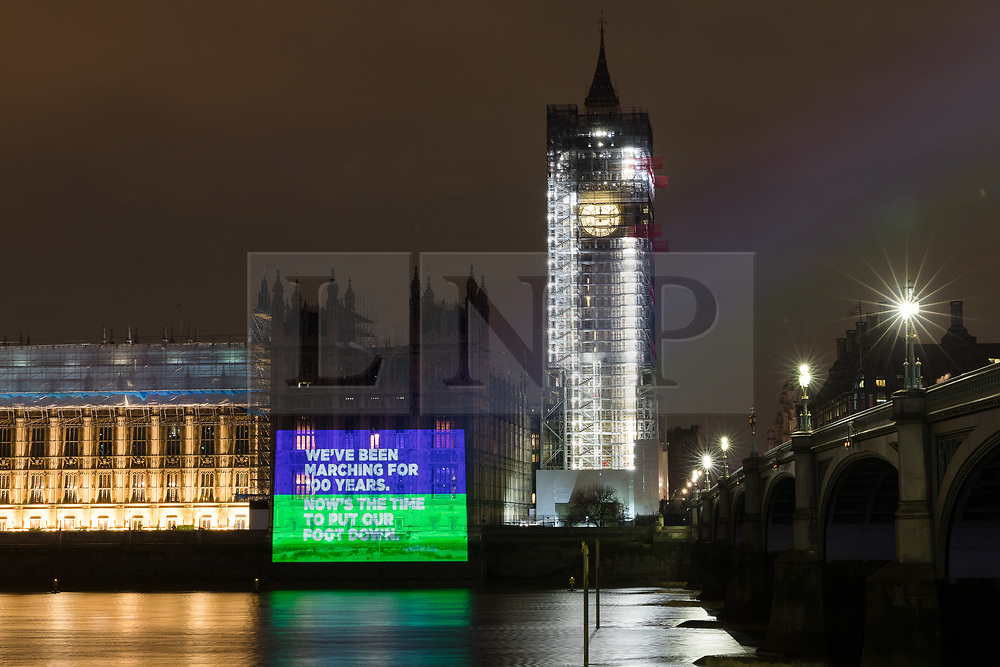 """© Licensed to London News Pictures. 06/02/2018. London, UK. A projection reading """"We've been marching for 100 years. Now's the time to put our foot down"""" onto the Palace of Westminster by the Women's Equality Party to mark the centenary of the 1918 Representation of the People Act, which passed on 6 February 1918. Photo credit: Vickie Flores/LNP"""
