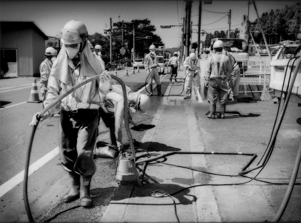 Decontamination work crew on the main highway that links highly radioactive Iitate-mura with Fukushima City and the sea.  Residents may return to Iitate-mura but, due to the radioactive fall out from Fukushima Daiichi Nuclear Power plant, the levels of radiation make it too dangerous to inhabit full time.  That said, some residents have apparently returned and refused to leave.  Iitate-mura, Fukushima Prefecture, Japan.