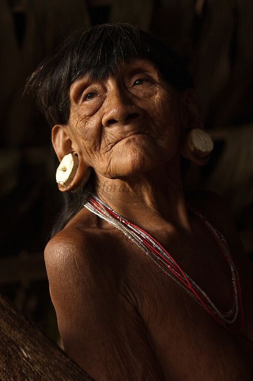 Huaorani Indian woman - Konta ñamaronko. Gabaro Community. Yasuni National Park.<br /> Amazon rainforest, ECUADOR.  South America<br /> She has the typical stretched ear lobes common amoung the Huaorani. They often wear balsa ear plugs.<br /> This Indian tribe were basically uncontacted until 1956 when missionaries from the Summer Institute of Linguistics made contact with them. However there are still some groups from the tribe that remain uncontacted.  They are known as the Tagaeri. Traditionally these Indians were very hostile and killed many people who tried to enter into their territory. Their territory is in the Yasuni National Park which is now also being exploited for oil.