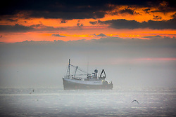 © Licensed to London News Pictures. 07/08/2020. Scarborough UK. A fishing boat heads to port through sea fog at dawn this morning on the Yorkshire coast. Photo credit: Andrew McCaren/LNP