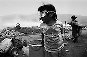 Municipal dump, Oaxaca, Mexico 1998 - A girl plays with a mask found in the dump while her grandmother and family make an existence by selling scavenged recyclable materials...In the municipal dump a self governed group of 80 individuals and families eke out a living.  Los Pepenadors (the Pickers) work in a landscape of garbage and flames, blanketed by toxic smoke, along side bulldozers and garbage trucks.  They do the impossible job of recycling what the rest of their society can't be bothered to deal with. ..