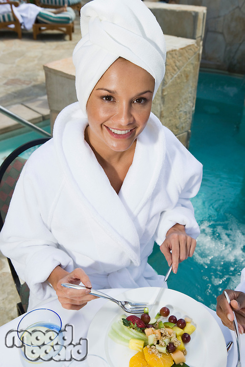 Portrait of woman in bathrobe, eating by pool