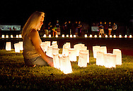 Goshen, New York - A woman kneels by luminaria in remembrance of cancer victims during the Relay for Life at Goshen High School on June 16, 2012. The Relay for Life is the American Cancer Society's signature fundraising event. Participants celebrate the lives of people who have battled cancer, remember loved ones lost, and fight back against the disease by raising money.