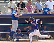 Kansas State's Barrett Rice (R) races down the first base line, as Jayhawk first basemen Preston Land (L) goes up high to catch a wild throw.  Rice was safe at fist.  The Wildcats held on to beat Kansas 5-4 at Tointon Stadium in Manhattan, Kansas, April 23, 2006.