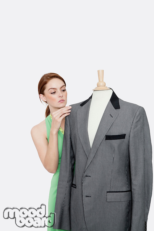 Young female fashion designer looking at blazer on tailor's dummy over gray background