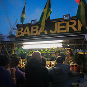Baba Jerk chicken stall in Ridley Road, it's night time and dinner time. Hackney carnival 2016 took place on a hot Indian summer's day, September 2016 with the streets full of partying people.
