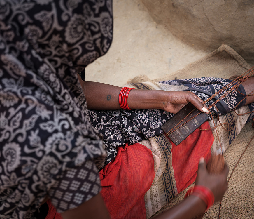 VARANASI, INDIA - CIRCA NOVEMBER 2018: Hands of woman with net from a fishing village close to Varanasi. Varanasi is the spiritual capital of India, the holiest of the seven sacred cities and with that many rituals and offerings are performed daily by priests and hindus.