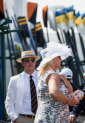 © Licensed to London News Pictures. 04/07/2018. Henley-on-Thames, UK. A woman in al elaborate hat stands next to rowing oars at day one of the Henley Royal Regatta, set on the River Thames by the town of Henley-on-Thames in England. Established in 1839, the five day international rowing event, raced over a course of 2,112 meters (1 mile 550 yards), is considered an important part of the English social season. Photo credit: Ben Cawthra/LNP