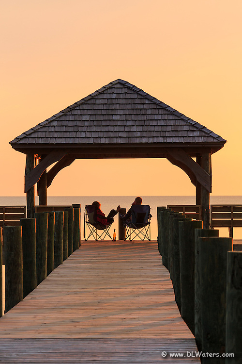 Silhouette of a couple relaxing under a gazebo watching the sunset on Currituck sound.