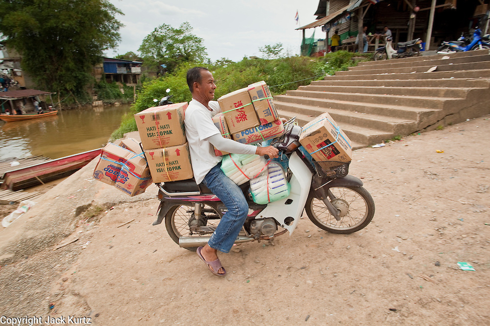 Sept. 27, 2009 -- SUNGAI KOLOK, THAILAND: A man rides a motorcycles loaded with imported goods brought to Thailand at an informal border crossing on the Kolok River in Sungai Golok, Narathiwat, Thailand. The Thai-Malaysia border in Narathiwat province sees a steady stream of cross border trade but tourism from Malaysia which once flourished for Malaysians who wanted to drink and enjoy other vices prohibited in Muslim Malaysia has all but stopped since violence by Muslim insurgents in south Thailand destroyed several tourist hotels. Photo by Jack Kurtz / ZUMA Press