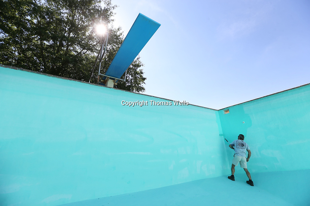 Shawn Roberts puts a fresh coat of paint on the interior walls of the deep end of the C.C. Agustus pool on North Green Street Tuesday morning. The pool gets fresh coat of paint and other maintance every spring.