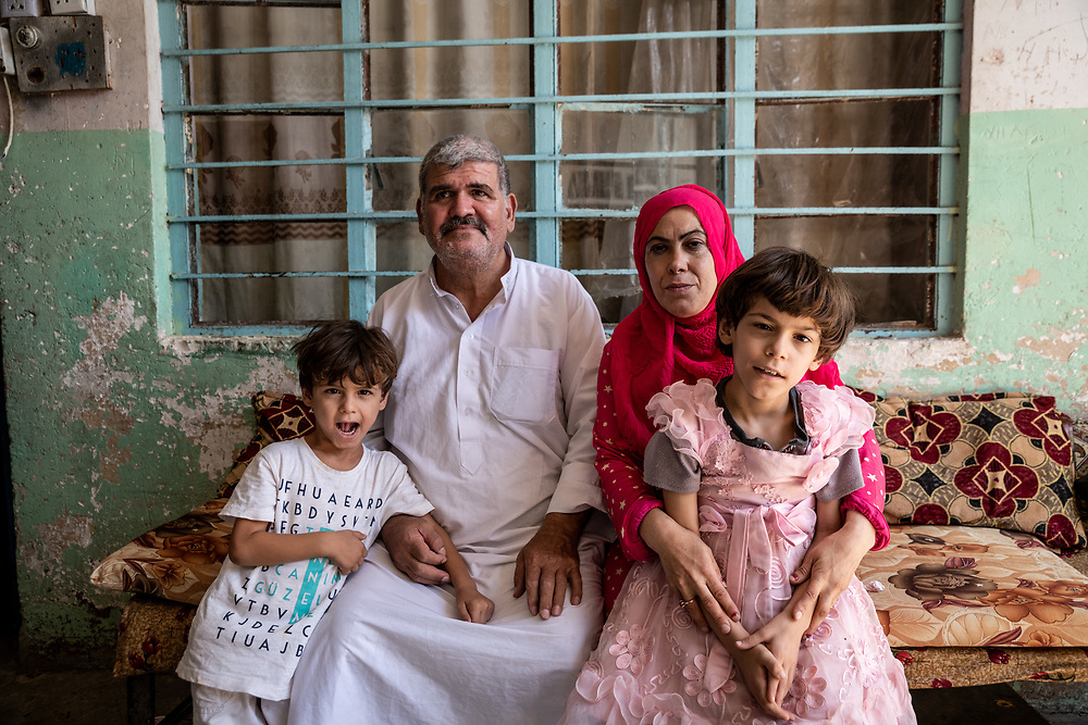 9 August 2018 – Mosul – Iraq – A family sits for a photo Inside a damaged home in al-Islah al Zirahee neighborhood of West Mosul. <br /> <br /> This home is amongst the houses due to be rehabilitated with the support of UNDP's Funding Facility for Stabilization (FFS). <br /> <br /> © UNDP Iraq / Claire Thomas