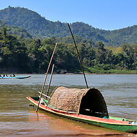 Thatched Canoe on Mekong River Shore in Ban Pak Ou, Laos <br />