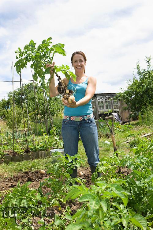Woman holding potatoes in garden portrait