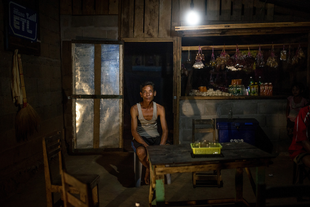 Xieng Pai, 54, is a shopkeeper in the village of Khoc Kham. He powers the light in his shop using a poratble water turbine. Having access to electricity allows him to keep his shop open longer than he could in the past.