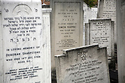 Headstones in a Orthodox Jewish cemetery in Enfield, North London. Space in the cemetery is limited and graves are very close together. The dates on the headstones are from the Jewish calendar.