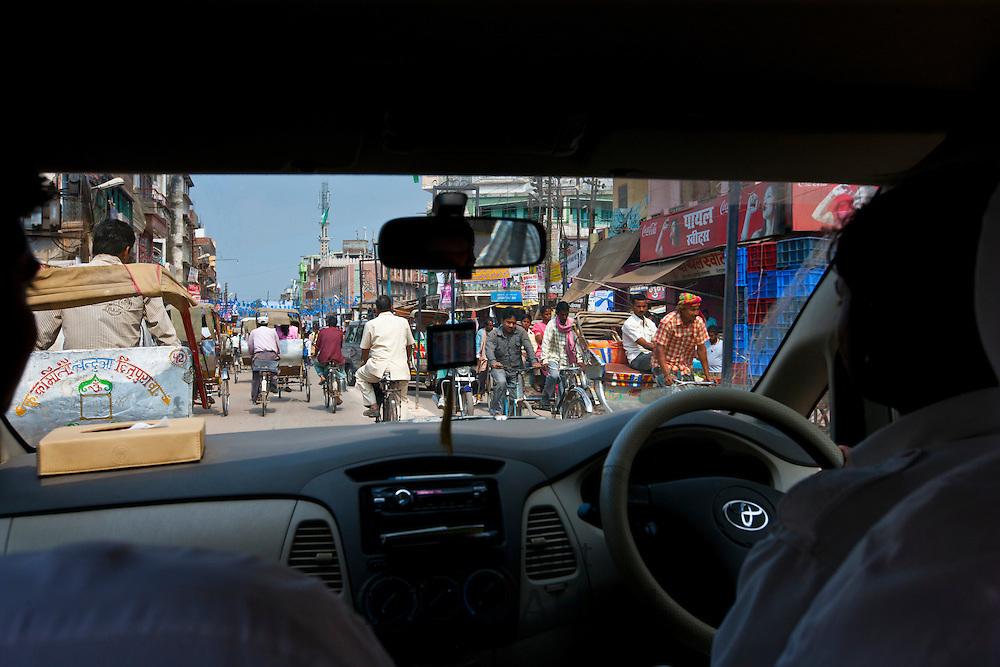Busy street scene viewed through taxi windscreen in city of Varanasi, Benares, Northern India