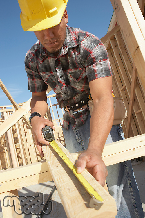 Construction Worker Measuring Timber