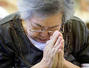 Keiko Komabayashi, 82, bows her head in prayer as she and other residents hold a minute's silence to commemorate the 3 month anniversary of the quake and tsunamis in which some 25,000 people were killed or remain missing  in Kamiashi, Iwate Prefecture, Japan on  11 June 20011.  .Photographer: Robert Gilhooly