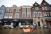 In Delft staat een bakfiets geparkeerd voor een cafe.<br /> <br /> In Delft a cargo bike is parked in front of a cafe.