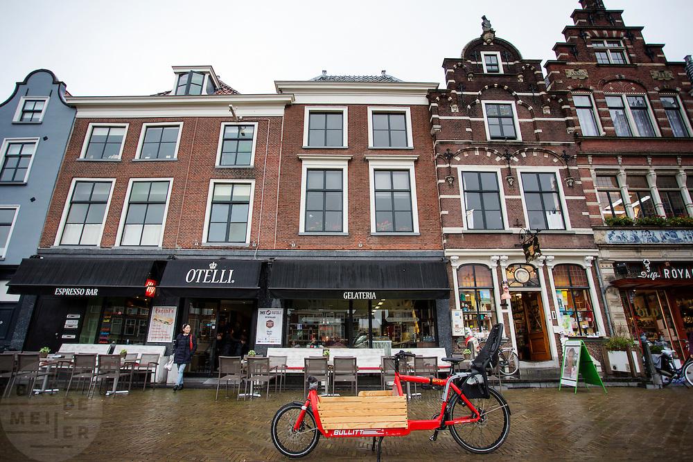 In Delft staat een bakfiets geparkeerd voor een cafe.<br /> <br /> In Delft a cargo bike is parked in front of a cafe.