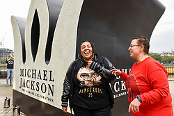 © Licensed to London News Pictures. 29/08/2018. LONDON, UK.  Michael Jackson fans dance next to a 13 foot high jewelled crown which has been installed on the South Bank to mark Michael Jackson's 60th birthday.  Photo credit: Stephen Chung/LNP