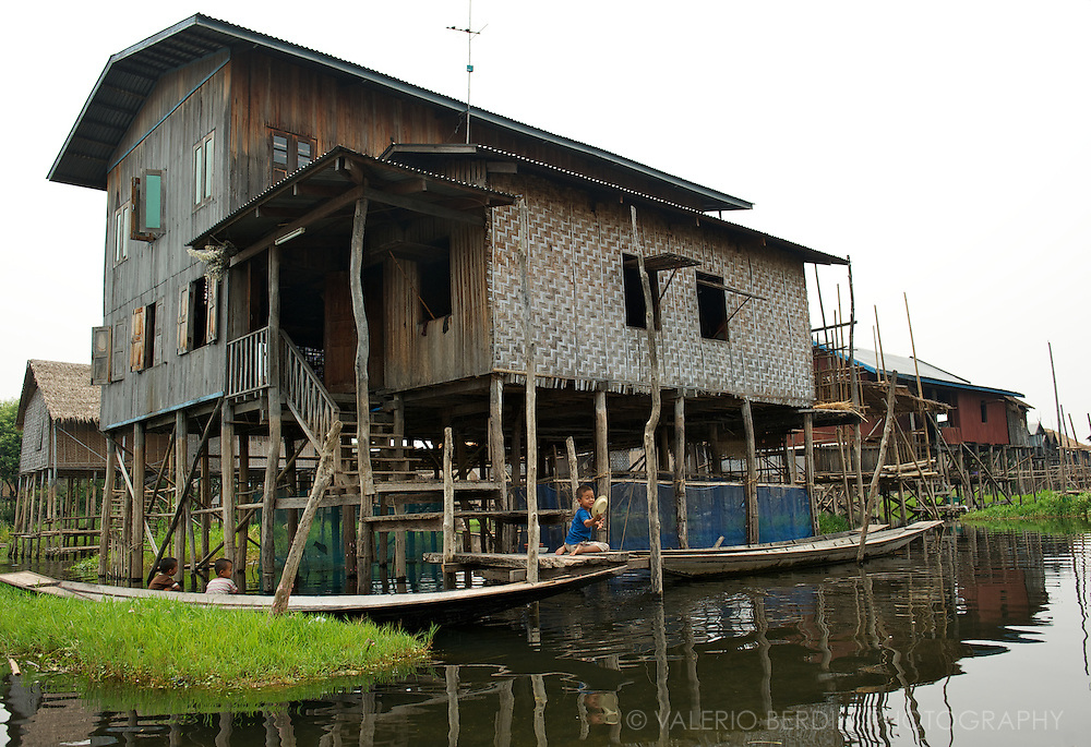 Children play on canoes docked next to a stilt house.
