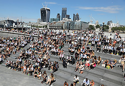 Image licensed to i-Images Picture Agency. 03/07/2014. London, United Kingdom. Office workers enjoy the hot weather on the Southbank in London. Picture by Stephen Lock / i-Images
