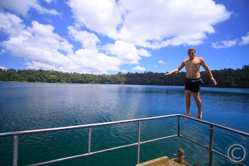 A young man jumps into the refreshing waters of Lake Eacham in the Crater Lakes National Park, the Atherton Tablelands, far north Queensland, Australia