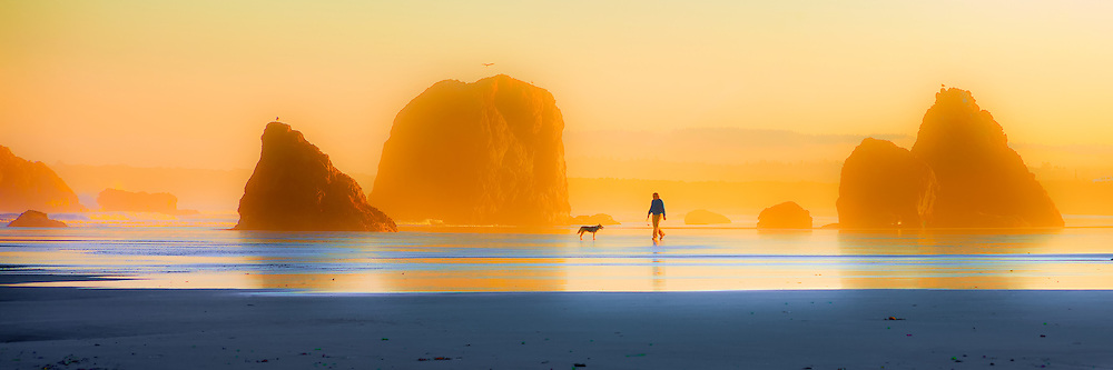 A man walks his  dog at Sunrise on Bandon Beach, OR