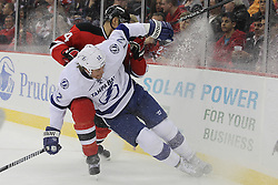 Mar 29; Newark, NJ, USA; Tampa Bay Lightning left wing Ryan Malone (12) and New Jersey Devils defenseman Bryce Salvador (24) battle for the loose puck during the second period at the Prudential Center.