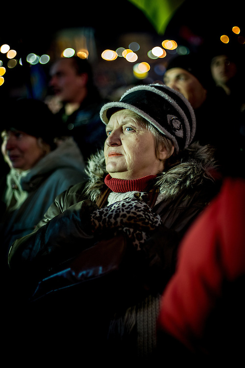 An old woman looks at the stage and listens to the speeches, on the Independance Square, at night.