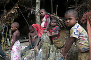 Maniq children play in the entrance of their cave that they are currently staying in until the end of the rainy season.<br /> <br /> Evidence suggests that the Maniq, a Negrito tribe of hunters and gatherers, have inhabited the Malay Peninsula for around 25,000 years. Today a population of approximately 350 maniq remain, marooned on a forest covered mountain range in Southern Thailand. Whilst some have left their traditional life forming small villages, the majority still live the way they have for millennia, moving around the forest following food sources. <br /> <br /> Quiet and reclusive they are little known even in Thailand itself but due to rapid deforestation they are finding it harder to survive on the forest alone and are slowly being forced to move to its peripheries closer to Thai communities.