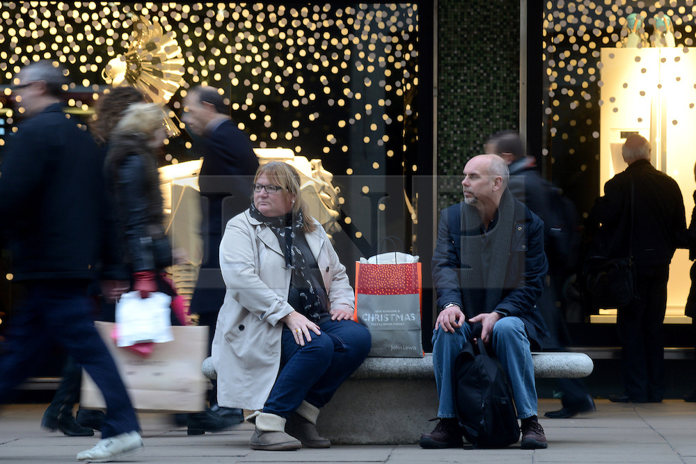 © Licensed to London News Pictures.05/12/2013. London, UK. Christmas shoppers take a rest on Oxford Street.Photo credit : Peter Kollanyi/LNP